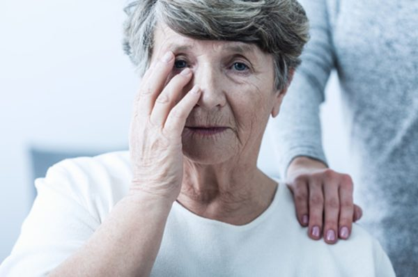 close up of a senior woman holding her hand up to her face as if in pain