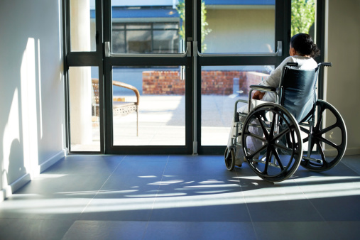An old woman sitting in a wheelchair at the the door of a nursing home