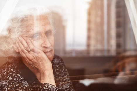 a nursing home resident holds her face in her hand as she stares out a window